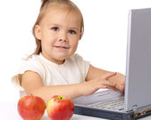 Cute little girl with laptop and two apples — Stock Photo