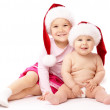 Two children wearing red Christmas caps and smile — Stock Photo #4236677