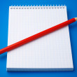 Blank notepad and a pencil on blue — Stock Photo