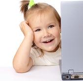 Schattig klein meisje is op zoek vanuit haar laptop — Stockfoto