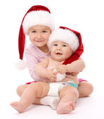 Two children wearing red Christmas caps and smile — Stock Photo