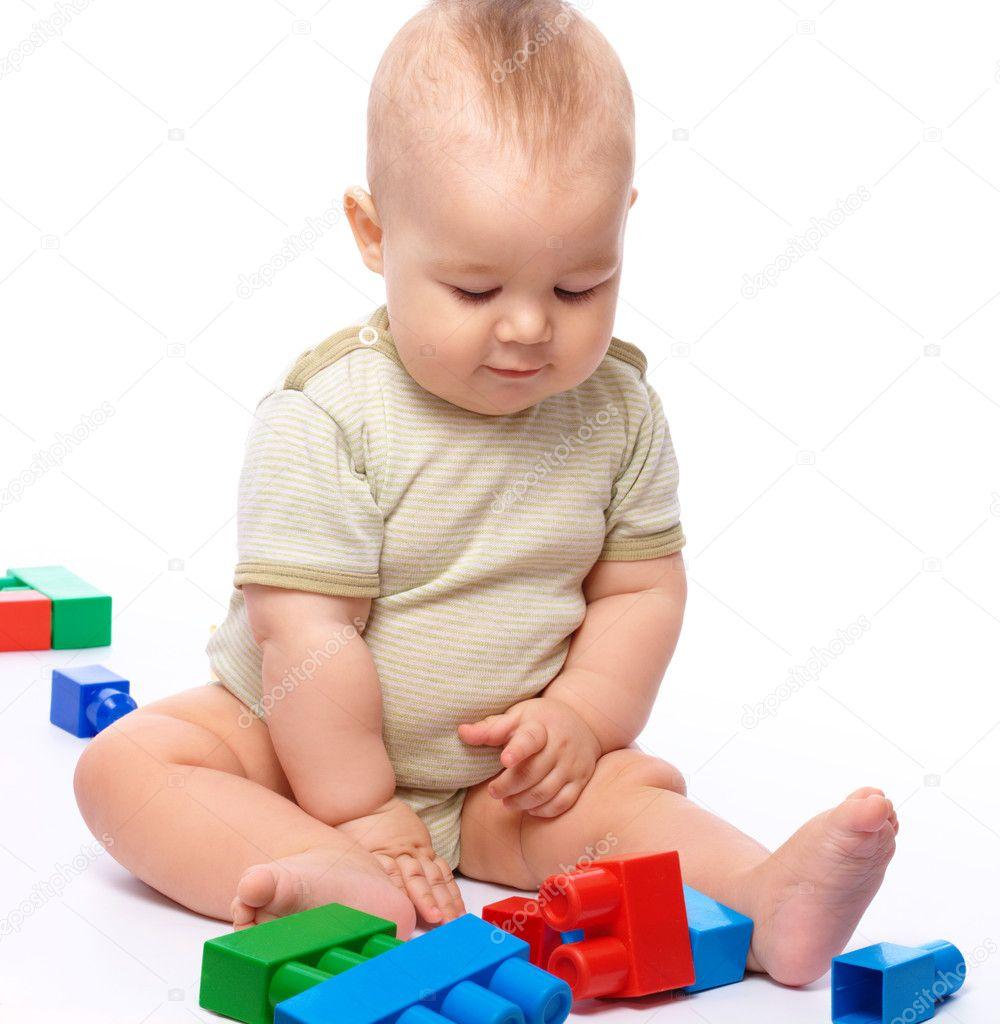 可爱的小男孩在玩坐在地上