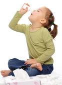 Little girl spraying her nose — Stock Photo