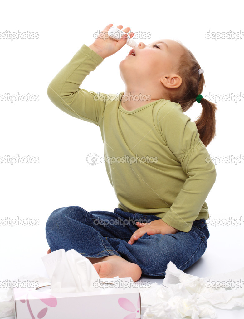 Little girl spraying her nose with nasal spray while sitting on floor, isolated over white  Stock Photo #4671246