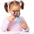������, ������: Girl is looking at euro banknote using magnifier