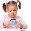 Постер, плакат: Girl is looking at euro banknote using magnifier