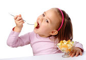 Little girl eats fruit salad — Стоковое фото