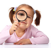Curious girl is looking through magnifying glass — Stock Photo
