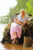 Young pensive woman sitting at river bank or lake shore — Stock Photo