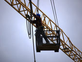 Worker on the arm of a crane — Stock Photo