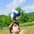 Soccer player juggling ball - Stock Photo