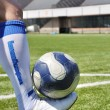Human leg and soccer ball on the grass field — Stock Photo