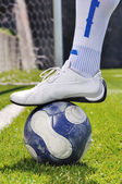 Human leg and soccer ball on the grass field — 图库照片