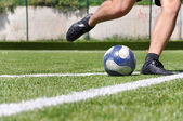 Human leg shooting soccer ball on the grass field — Stock Photo