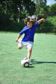 Young boy shooting soccer ball — Stock Photo