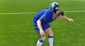 Soccer player holding ball on the neck — Стоковое фото