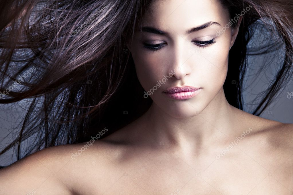 Young woman looking down with flying hair  Stock Photo #4590676