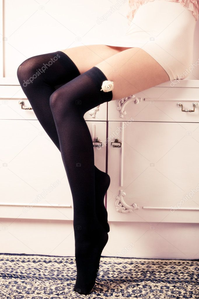 Female long legs in black hosiery and short pink dress, sitting on dresser, indoor shot — Stock Photo #4969695