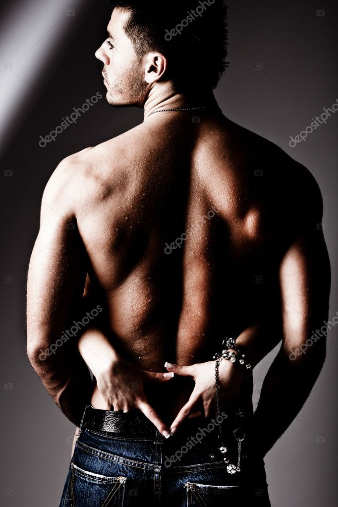 Shirtless wet muscular man in jeans and woman hands, studio shot — Stock Photo #5167795