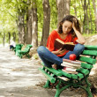 Stock Photo: The girl with books sitting on a bench