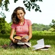 Stock Photo: The girl with books sitting on a grass