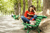 The girl with books sitting on a bench — Stock Photo
