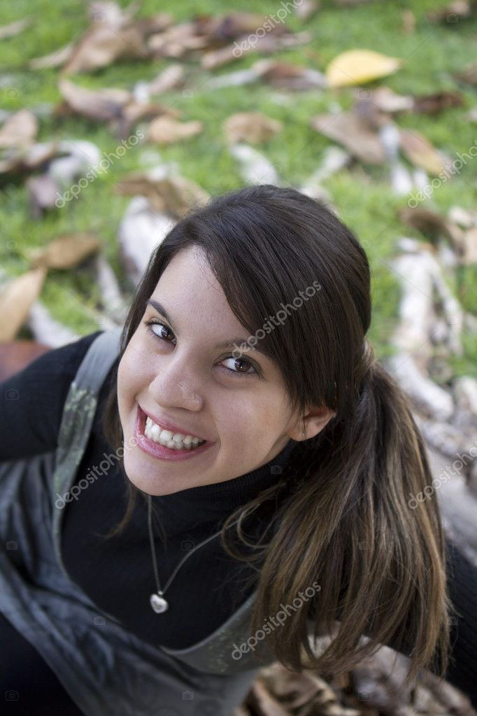 Close-up top view of a young beautiful girl smiling in a green park  Stock Photo #5339964