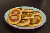 Some mini pizzas with olive, cheese and tomato sauce on a white plate ready — Stock Photo