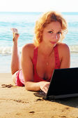 Girl on the beach with a computer — Стоковое фото