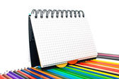 Notebook in a cell with pencils — Stock Photo