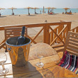 Wine bottle and glasses on a table at a beach — Stok fotoğraf