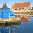 Houses and boat next to a river with reflection - Stock Photo