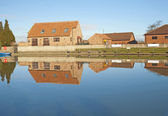 Houses next to a river with reflection — Stock Photo