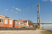 Housing next to a large suspension bridge — Stock Photo