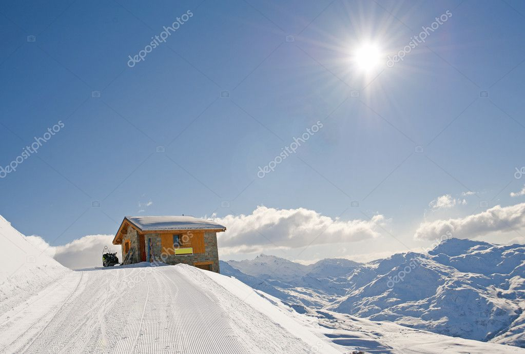 Mountain hut on edge of mountain with landscape view and a skidoo bike — Stock Photo #5031796