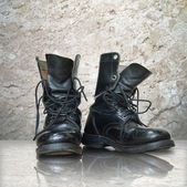 Old black boot on white marble — Stock Photo