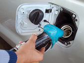 Hand holding blue fuel pump — Stock Photo