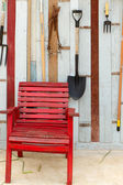 Red chair. In front of the old wooden walls. — Stock Photo