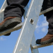 Man on a ladder - Stock Photo