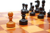 One white pawn fights against black army on chess board. — Stock Photo