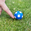 Man hand playing role of soccer player with small blue ball — Stock Photo