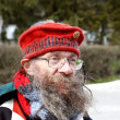 Homeless senior in funny red cap - Stock Photo