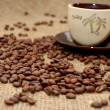 Stock Photo: Coffee beans on focus and cup with cofee at background
