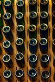 Old aged wine in bottles at Wooden pedestal for wine making. — Stock Photo