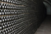 Tunnel with old aged wine in dusted bottles. Winemaking plant. — Stock Photo