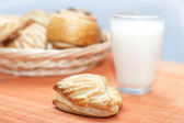 Puff pastry and glass with milk on bamboo place mat — Stock Photo