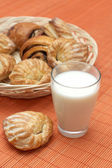 Glass with fresh milk and puff pastry on bamboo place mat — Stock Photo