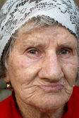 Sad old woman in the yellow blouse — Stock Photo