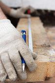 Händer i skyddshandskar med penna och meter åtgärd linjal — Stockfoto