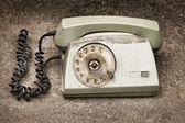 Grunge: old broken phone on asphalt background — Stock Photo